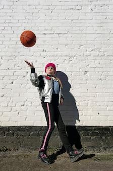 Спортивная девушка играет с баскетбольным мячом у белой кирпичной стены.