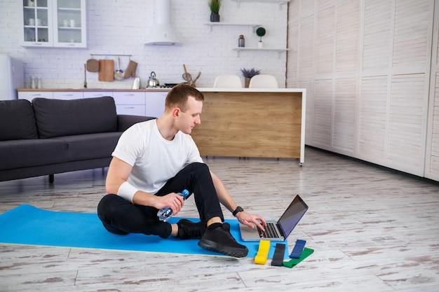 Tシャツを着たスポーティな男性が、ミニマルなインテリアの広々とした明るいアパートで、自宅でスポーツに出かけます。インターネットスポーツ