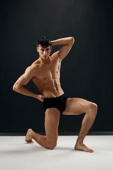 暗い背景に黒いパンティーで裸の体を持つスポーティな男は彼の膝の上にあります