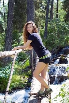 森の中に立つスポーツショーツ姿のスポーティな細身女性