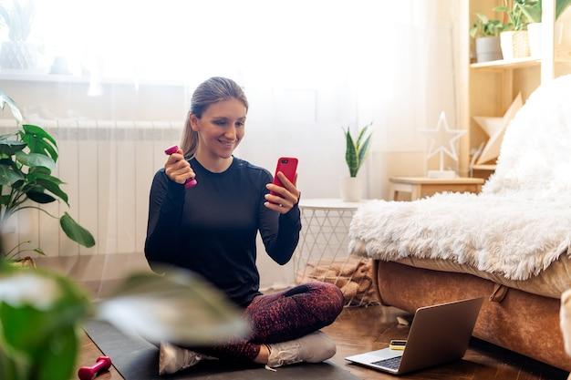 Спортивная женщина в спортивной одежде и наушниках работает и использует ноутбук дома в гостиной