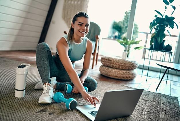 Спортивная женщина в спортивной одежде сидит на полу с гантелями и протеиновым коктейлем или бутылкой воды и использует ноутбук дома в гостиной. концепция спорта и отдыха.