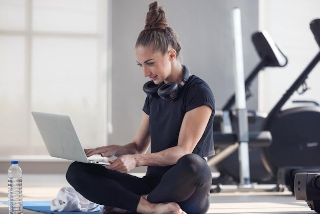 운동복을 입은 스포티 한 여성이 덤벨과 단백질 쉐이크 또는 물 한 병을 들고 바닥에 앉아 거실에서 집에서 노트북을 사용하고 있습니다. 스포츠 및 레크리에이션 개념.