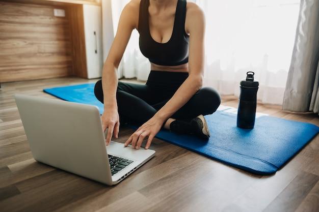 운동복을 입은 스포티 한 여성이 덤벨과 단백질 쉐이크 또는 물 한 병을 들고 바닥에 앉아 노트북을 사용하고 있습니다. 스포츠 및 레크리에이션 개념.