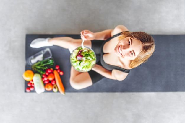 운동복에 스포티 한 여자가 건강 식품과 함께 바닥에 앉아있다.