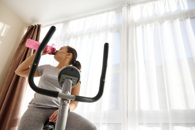 Спортивная женщина сидит на велотренажере и пьет воду, чтобы избежать обезвоживания после кардиотренировки.