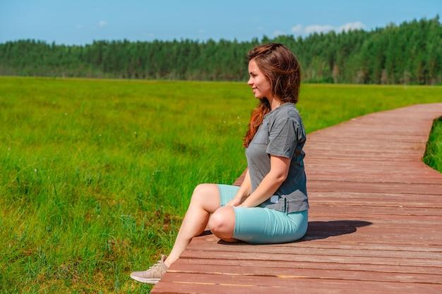 Спортивная молодая женщина идет по живописной деревянной пешеходной дорожке через болото с высокой травой