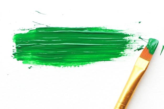 汚れた濃い緑色のアクリル絵の具のスポットとその隣の絵筆