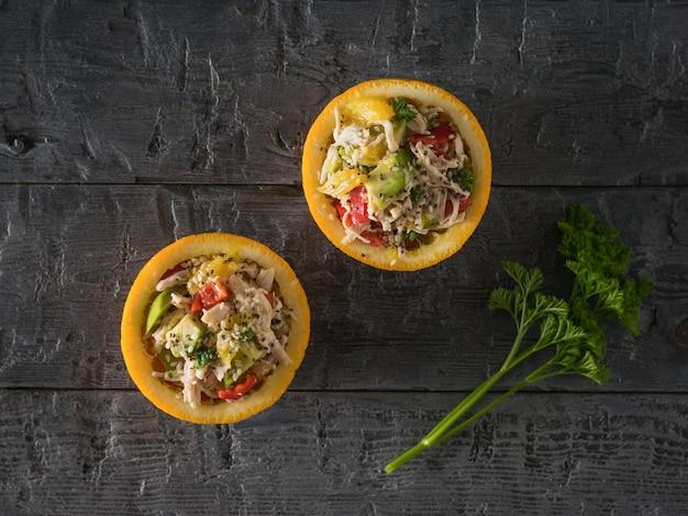 Веточка петрушки и половинка апельсина с салатом из авокадо и курицей. диетическое питание из тропических фруктов и курицы.