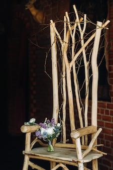 ライラックと白いバラの春のウェディングブーケは、装飾的な木製の椅子の上にあります。ウェディングブーケ、詳細、結婚式、装飾。