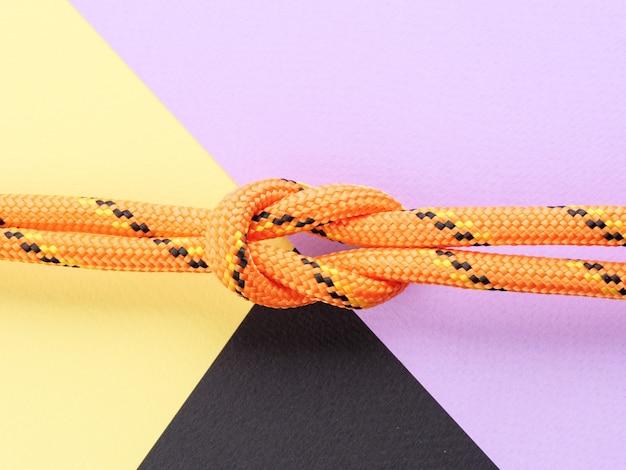 Квадратный узел из нейлоновой оранжевой веревки на пастельно-фиолетовом фоне.