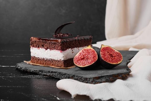 돌 플래터에 초콜릿 치즈 케이크의 사각형 조각.