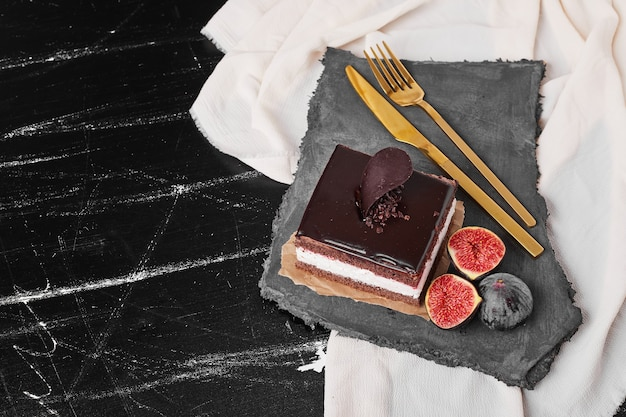 石の大皿にチョコレートチーズケーキの正方形のスライス。