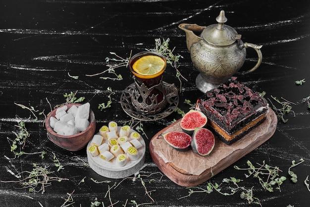 お茶のグラスと木の板にチョコレートチーズケーキの正方形のスライス。