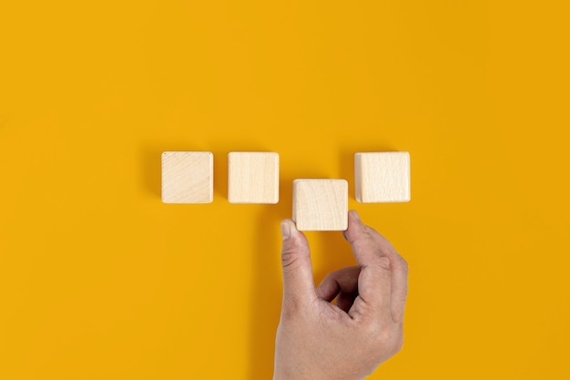 노란색 배경에 정사각형 나무 블록이 놓여 있고 손이 세 번째 나무 블록을 집어 들고 있습니다. 나무 블록 개념, 텍스트, 포스터, 모형 템플릿 복사 공간이 있는 배너.
