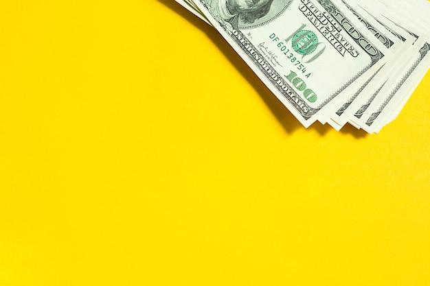 노란색 배경에 100달러 지폐의 스택. 개념 비즈니스, 금융, 투자, 현금 지불, 저축 및 부. 복사 공간