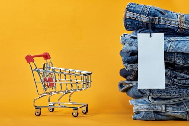 Стопка синих джинсов с белой пустой биркой на желтом фоне. тележка для покупок с разноцветными кубиками. слово продажи написано на кубиках. концепция продаж. куча стильных модных джинсовых брюк.