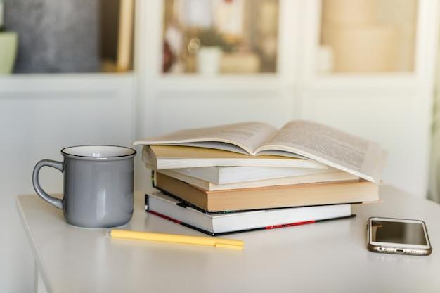 白いテーブルの上に本の山、お茶のマグカップ、そして携帯電話。の概念と教育。