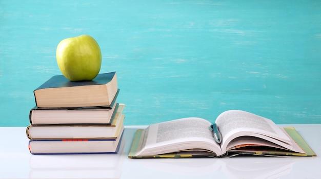 Стопка книг, открытая книга, зеленое яблоко на столе.