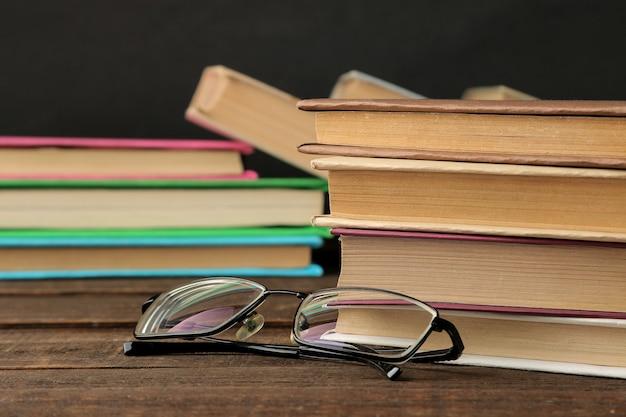Стопка книг и очков на коричневом деревянном столе и на черном фоне. старые книги. образование. школа. учиться
