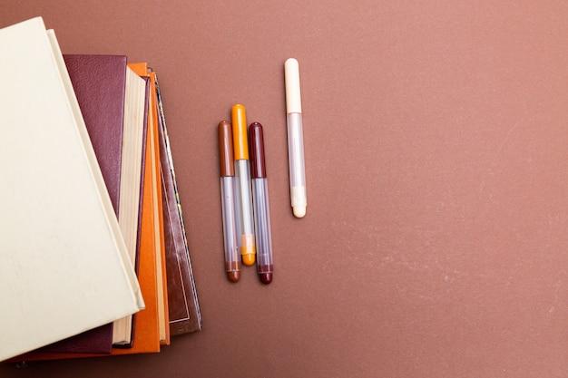 베이지 색에 책과 멀티 컬러 펜 스택