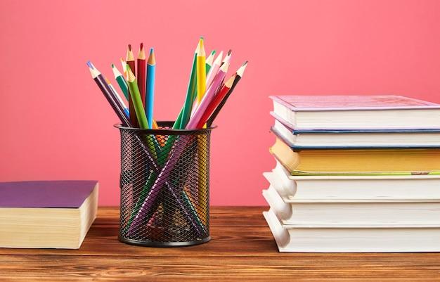 Стопка книг, цветные карандаши