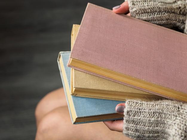 Стопка книг в руках женщины Premium Фотографии