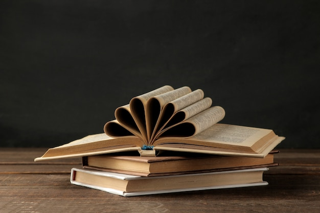 Стопка книг на коричневом деревянном столе и на черном фоне. старые книги. образование. школа. учиться