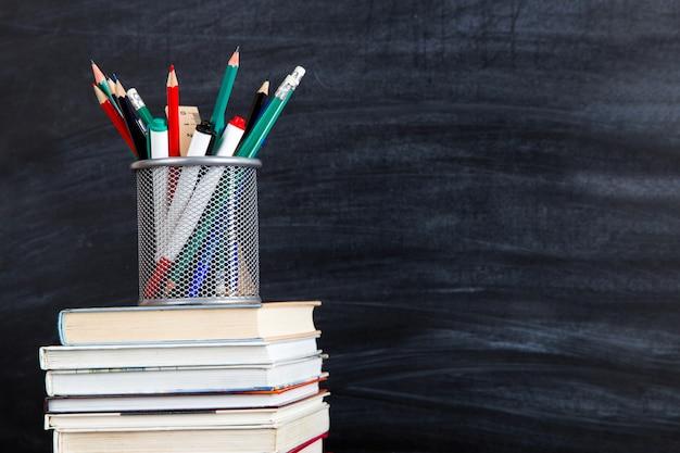 Стопка книг, поверх стойки с ручками и карандашами, против черной доске, копией пространства.