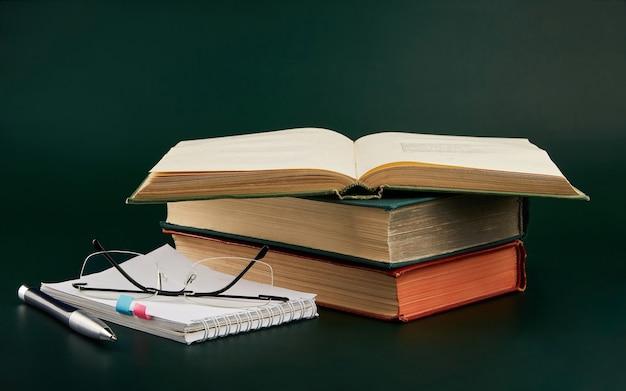Стопка книг с блокнотом и ручкой