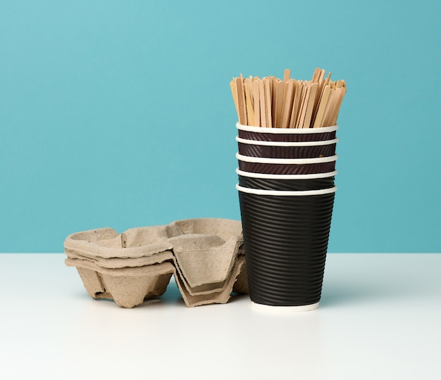 茶色の使い捨て紙コップのスタックと白いテーブル、青い背景の上のスタンド。持ち帰り用の道具、無駄ゼロ