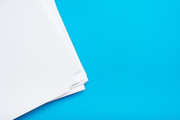 Стог чистой белой бумаги на таблице на голубой предпосылке. пустые страницы готовы для печати и записи. вид сверху