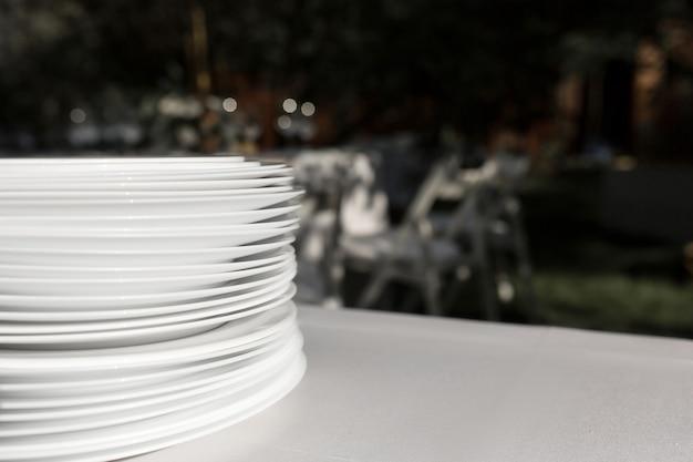 きれいな白いプレートのスタックは、屋外で白いテーブルクロスとテーブルの上に立っています