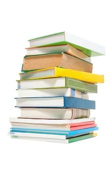 白い背景で隔離のカラフルな本や雑誌のスタック。