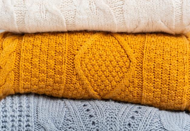 Стопка уютных вязаных осенне-зимних свитеров желтого, белого, синего цветов. уборка и организация пространства, одежды. гардероб.