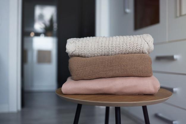 옷장의 배경에 대해 방의 나무 테이블에 아늑한 니트 스웨터 더미.
