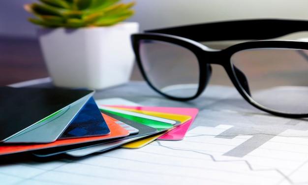 眼鏡をかけたテーブルの上のクレジットカードのスタック。カードを使用した銀行業務の概念