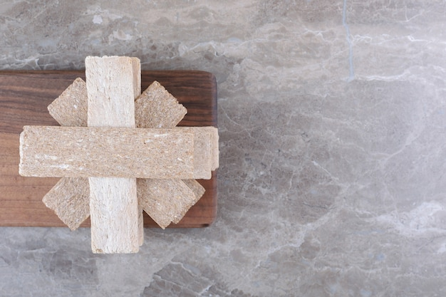 Стопка хрустящих хлебцев на деревянной доске, на мраморном фоне.