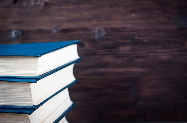木製の背景に濃紺の本のスタック