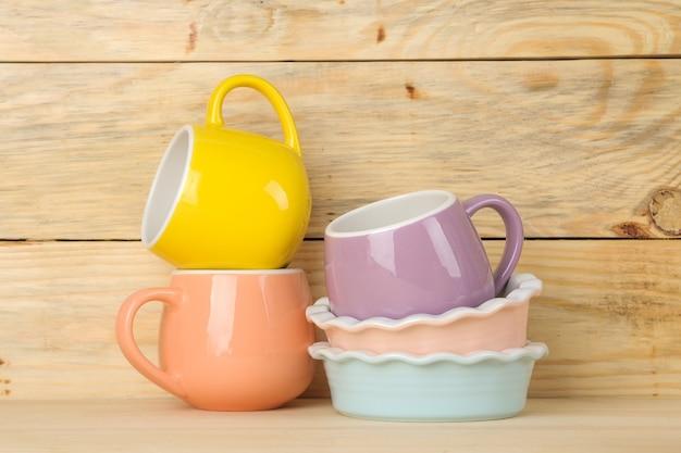 Стопка посуды. цветная посуда на натуральном деревянном столе. разноцветные чашки и миски.