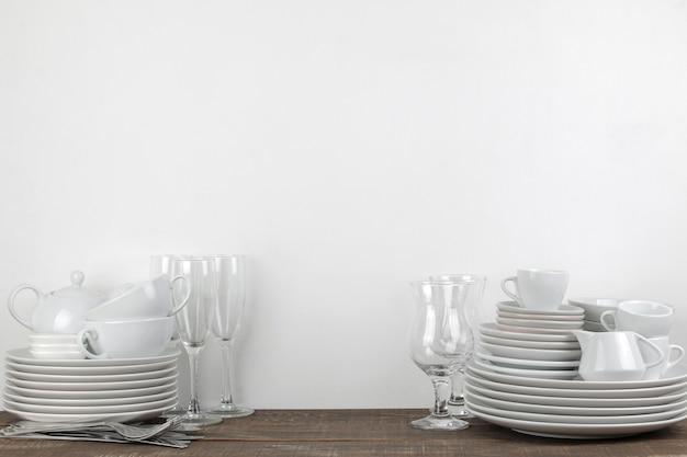 Стопка посуды. посуда на коричневый деревянный стол. посуда для сервировки стола. тарелки и столовые приборы, чашки и чайник, стаканы. с пространством для текста