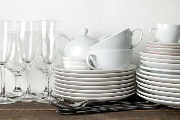 Стопка посуды. посуда на коричневый деревянный стол. посуда для сервировки стола. тарелки и столовые приборы, чашки и чайник, стаканы.