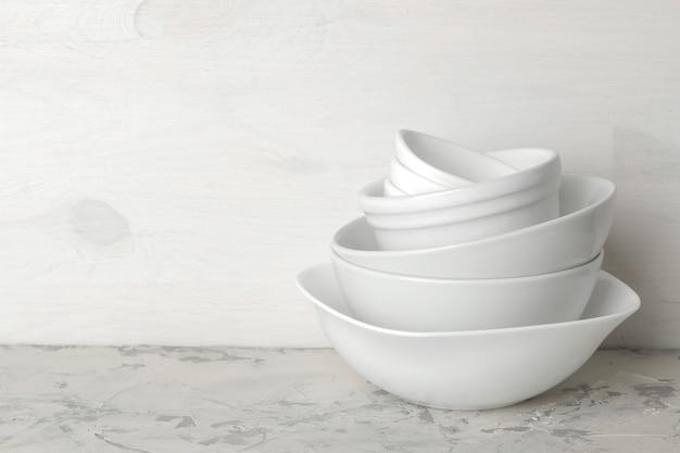 Стопка посуды. посуда на светлом фоне бетона. посуда для сервировки стола. белые миски в стопке. место для текста