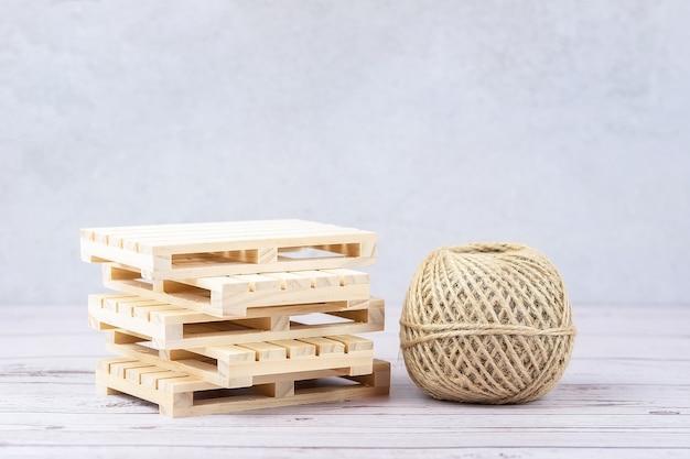 Стек пустых деревянных поддонов и веревка на серой поверхности