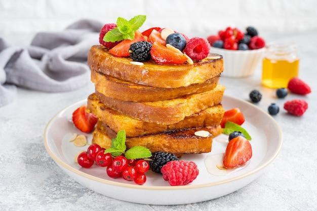 灰色のコンクリートの背景に新鮮なベリー、アーモンドの花びら、蜂蜜とプレート上のフレンチトーストのスタック。おいしい朝食。スペースをコピーします。