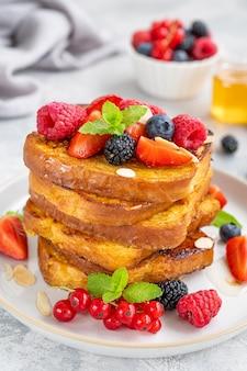 新鮮なベリー、アーモンドの花びら、蜂蜜とプレート上のフレンチトーストのスタック