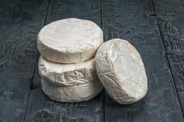 Стог свежеприготовленных сыров камамбер на деревянном столе.