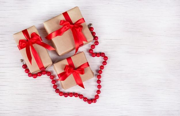 ギフト用の箱と白い木製の背景に赤いサンゴのネックレスのスタック
