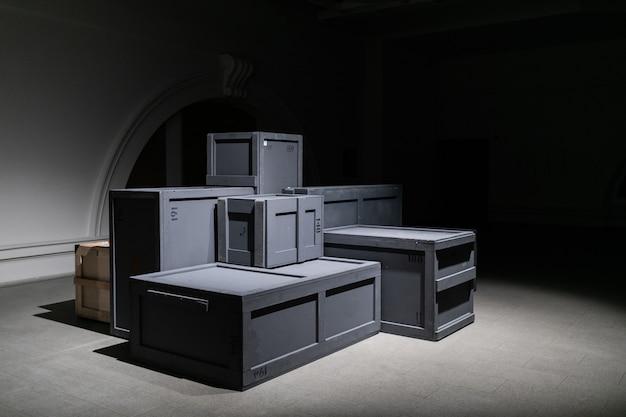Стопка серых деревянных ящиков разных размеров в огромном темном зале склада или музейного хранилища. концепция логистики и распределения