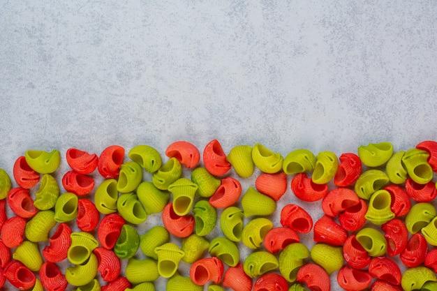 大理石の上に、緑と赤のパイプパスタのスタック。